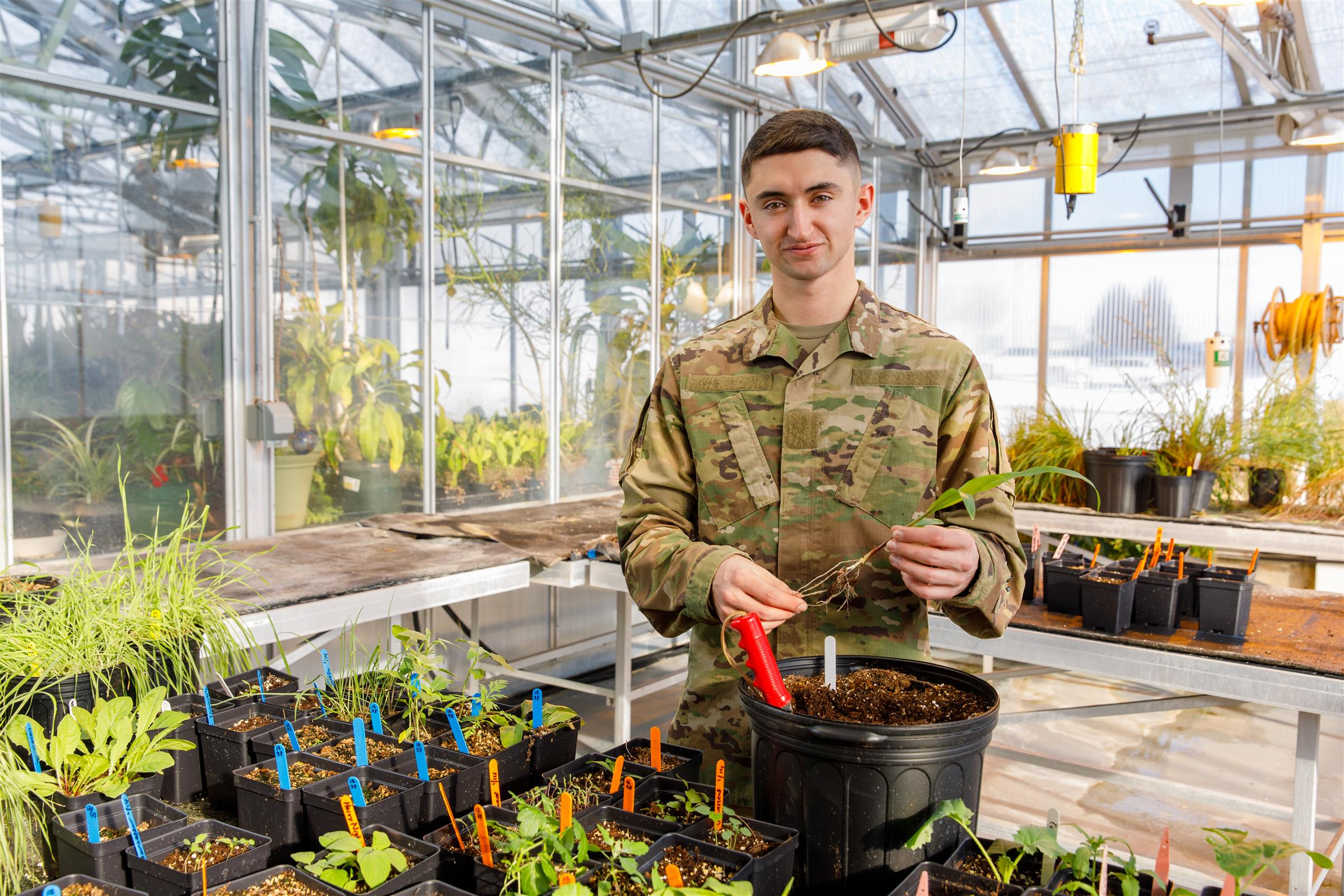 Military student in uniform holding a plant surrounded by plants in pots inside a greenhouse